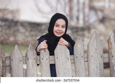 Little Girl Peeking Over an Old Wooden Fence with a Smile While Looking at the Camera.