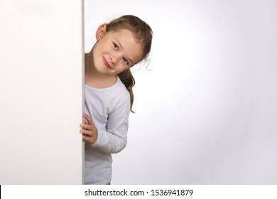 Little girl peeks out from behind a wall and looks mischievously