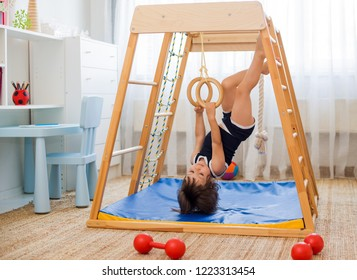 little girl performs gymnastic exercises on a wooden home sports complex stairs, rings and rope. Children's sports exercises. Physical education of children at home.