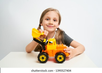 Little girl photographed against white background isolated is playing with toy bulldozer