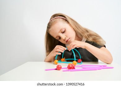 Little girl photographed against white background wearing school uniform dress isolated trying to solve geometric puzzle