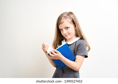 Little girl photographed against white background wearing school uniform dress isolated holding open blue book