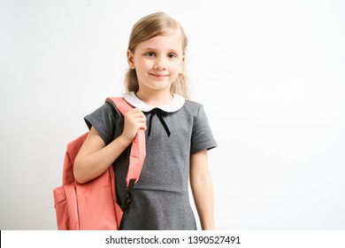 Little girl photographed against white background wearing school uniform dress isolated holding a coral backpack on one shoulder