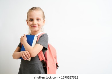 Little girl photographed against white background wearing school uniform dress isolated holding a coral backpack on both shoulders and book