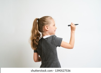 Little girl photographed against white background wearing school uniform dress isolated is mocking writing with marker
