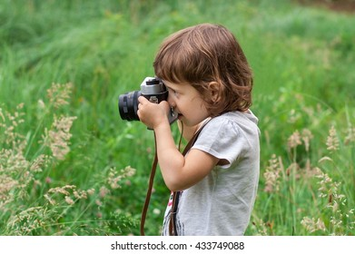 Little girl is photographing flowers in green grass by means of vintage camera.
