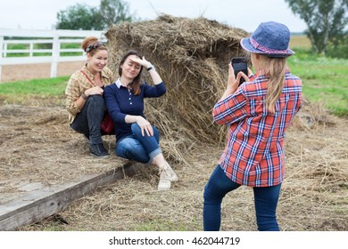 Little girl photographing of two women near the hay
