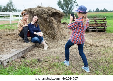 Little girl photographing of two women near the hay with mobile phone