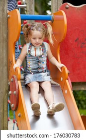 A little girl in pigtails is about to go down a slide.