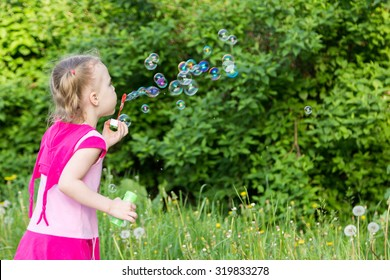 little girl with pigtails blows soap bubbles in park