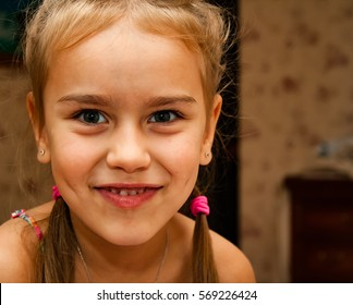 Little girl with pigtails and dimpled smiles and laughs. Laughing little girl.