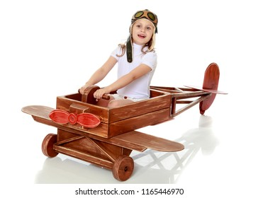 A little girl in a pilot's cap is playing in a large wooden plane. The concept of a happy childhood, games in the family and in kindergarten. Isolated on white background.