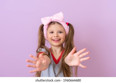 A little girl with a pink bow on her head shows her hands.
