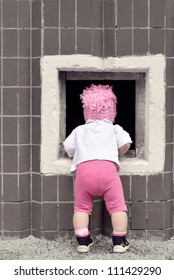Little girl in pink cap looking into a hole in the wall