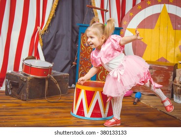 Little girl in pink costume at circus. Studio shot.