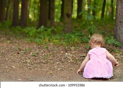 Little girl in pink dress gathering acorns in the forest