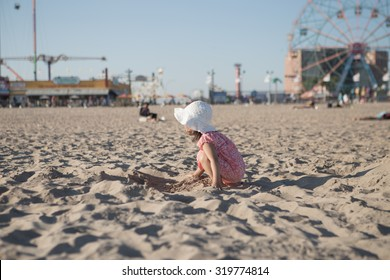 Little girl in pink dress playing with sand on the beach in Coney Island, Brooklyn, NY, USA. Photographed in September 2015.