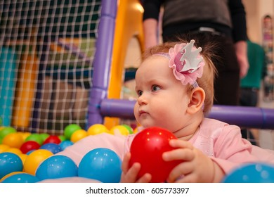 Little girl in pink dress plays with balls. Girl playing in colorful balls