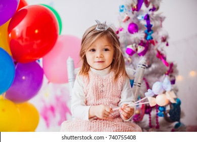 Little girl in pink dress plays in the room with pink Christmas tree