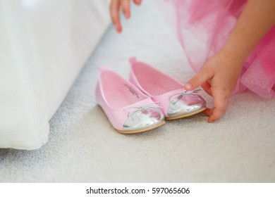 A little girl in a pink dress is preparing to try two shoes with a ball