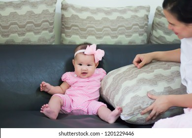 Little girl in a pink dress sits on a chair with a big pillow.