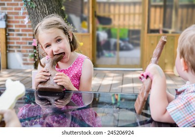 A little girl in a pink dress sits outside taking a big bite out of a large chocolate bunny on Easter day during the spring season.  Part of a series.