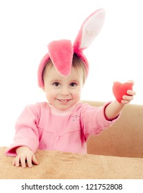 The little girl with pink ears bunny and a heart in his hand on white background