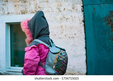 A little girl in pink jacket with grey hood and backpack with sparkles through a spooky streets with dirty walls on the building. Scary. Dangerous. Unsafe. Security. Alone. Outdoor. Loneliness