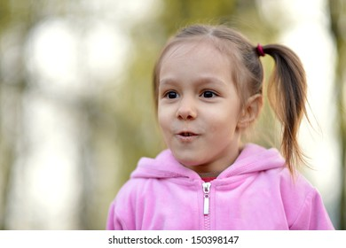 little girl in pink on a walk in the park
