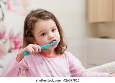 Little girl in pink pyjamas in bathroom brushing teeth