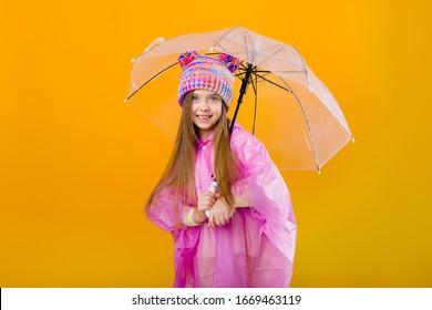 little girl in a pink raincoat and a knitted hat is holding an umbrella on a yellow background