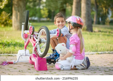 little girl with a pink safety helmet learns how to fix  bike