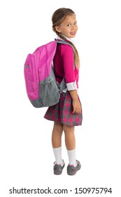 Little girl in pink school uniform with a backpack looking over right shoulder and smiling, isolated