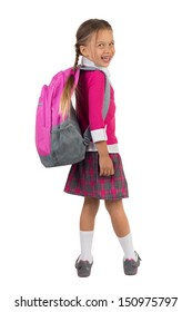 Little girl in pink school uniform with a backpack looking over right shoulder and laughing, isolated