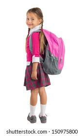 Little girl in pink school uniform with a backpack looking over left shoulder and smiling, isolated