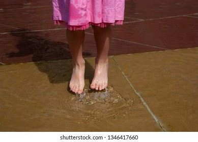 A little girl in the pink skirt is jumping on the water.