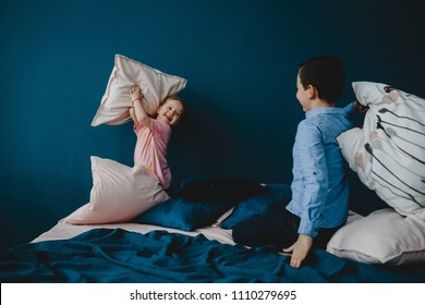 Little girl in pink t-shirt and boy in blue shirt fight with pillows on the bed