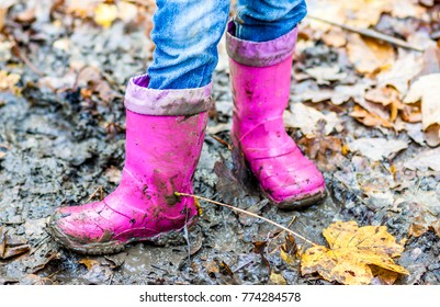 Little girl with pink wellys in the puddle on the forest