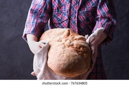 Little girl in plaid shirt holding freshly baked crusty homemade ciabatta bread. Dark background