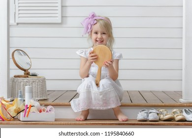 Little girl play in the beauty salon on at home on the porch