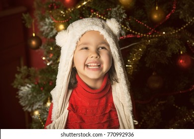 A little girl play with christmas toys in home interior. Child smiles and laughs.