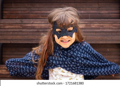 Little girl play in costume mask of scary superhero. Childhood