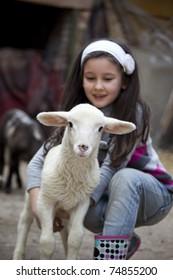 Little girl play with newborn lamb in a farmyard