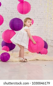 Little girl play with paper balls in the birthday party
