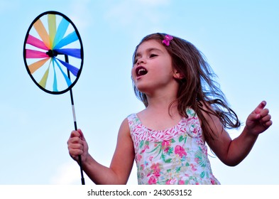Little girl play with pinwheel  toy windmill outdoors. concept photo seasonal and weather