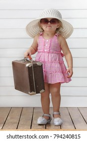 Little girl play with suitcases and dream to go on a trip