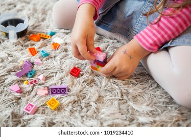 Little girl play with toy blocks on floor at home