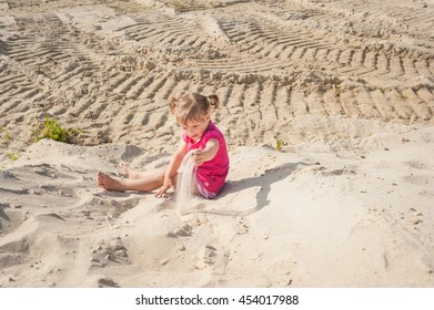 The little girl is played by sand. Happy childhood