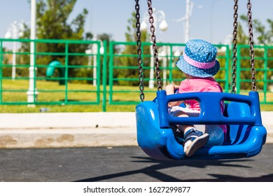 a little girl in a playground on a swing in a blue hat looking back in a sunny day.