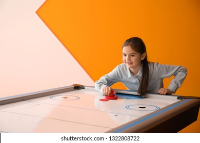 Little girl playing air hockey indoors